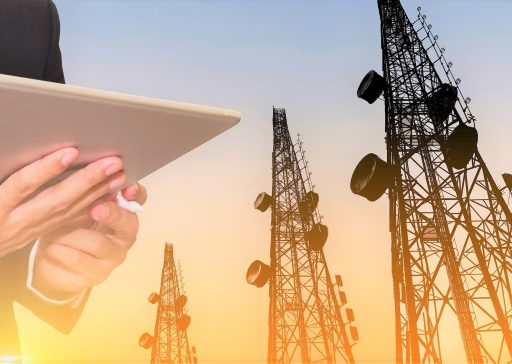 Businessman working on digital tablet, with satellite dish telecom network on telecommunication tower in sunset, telecommunication in business and development